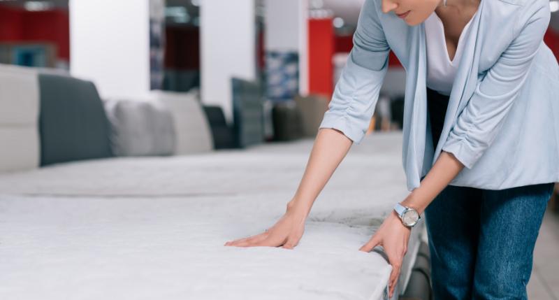 woman touching orthopedic mattress in furniture shop
